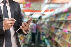 Businessman using the tablet on Abstract blurred photo of book store background Stock Photo