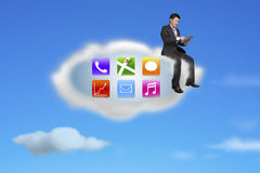 Businessman using tablet on app icons cloud with nature sky Royalty Free Stock Images