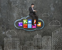 Businessman using tablet on black cloud with app icons Stock Images