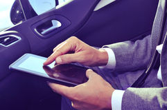 Businessman using a tablet in a car Stock Photo