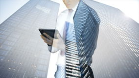 Businessman using tablet with cityscape overlay stock video footage