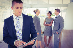 Businessman using tablet with colleagues behind him Royalty Free Stock Photo