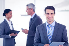 Businessman using a tablet  with colleagues behind in office Stock Photography