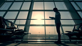 Businessman using tablet computer at the airport. silhouette of a man traveler with backpack. business and travel stock footage