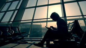 Businessman using tablet computer at the airport. silhouette of a man traveler with backpack. business and travel stock video footage