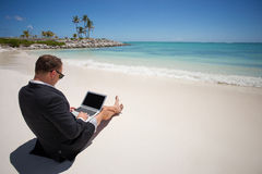 Businessman using tablet computer on the beach Royalty Free Stock Photos