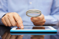 Businessman using tablet computer  with magnifying glass . Cauti Stock Photo