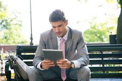 Businessman using tablet computer outdoors Royalty Free Stock Image