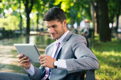Businessman using tablet computer outdoors Royalty Free Stock Images