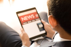 Businessman using tablet computer, reading news Stock Image