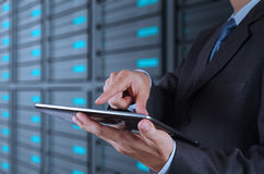 Businessman  using tablet computer and server room background. Businessman hand using tablet computer and server room background Royalty Free Stock Photography