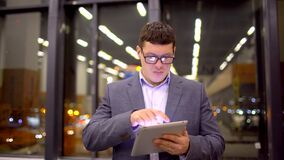 Businessman using tablet computer touchscreen in the night office. Businessman working on tablet computer standing by window in office at night. 4 k. Young stock footage