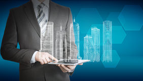 Businessman using tablet with 3d model of city. On abstract blue background Royalty Free Stock Photography
