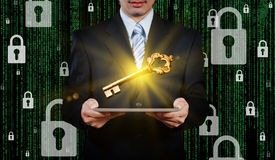 Businessman using tablet with gold key Stock Photo