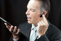 Businessman Using Tablet & Headset Earpiece. Royalty Free Stock Photo