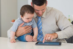 Businessman using tablet while holding baby Stock Photo