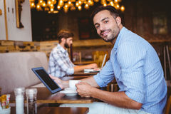Businessman using tablet while holding cup of coffee Royalty Free Stock Photos