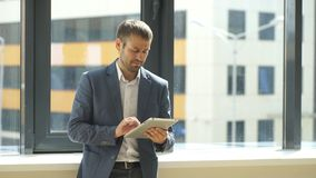 Businessman is using tablet in the office near the window. A successful businessman is using tablet in the office near the window stock video footage