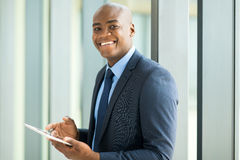 Businessman using tablet pc. Cheerful young african american businessman using tablet pc Royalty Free Stock Photos