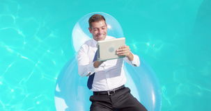 Businessman using tablet pc on inflatable. In the pool stock video footage
