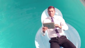 Businessman using tablet pc on inflatable. In slow motion stock video