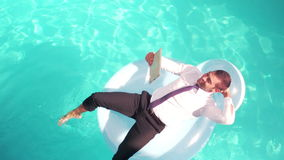 Businessman using tablet pc on inflatable. In slow motion stock video footage