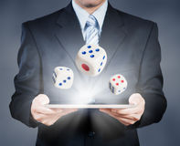 Businessman using tablet showing dice Royalty Free Stock Images