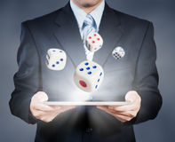 Businessman using tablet showing dice, risk management Royalty Free Stock Image