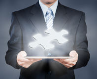 Businessman using tablet showing jigsaw piece, business decision Royalty Free Stock Photo