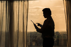 Businessman using tablet. Silhouette of Asian businessman using tablet at sunset stock photography