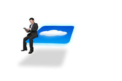Businessman using tablet sitting on cloud icon with white backgr Royalty Free Stock Photography