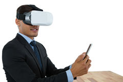Businessman using tablet while wearing vr glasses. At table against white background Royalty Free Stock Photo