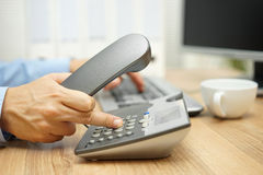 Businessman is using  telephone and computer at the same time Royalty Free Stock Images