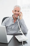 Businessman using telephone in front of laptop at office desk Stock Photos