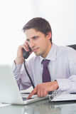 Businessman using telephone and laptop at desk Royalty Free Stock Images