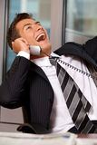 Businessman using telephone in office, smiling Stock Photography