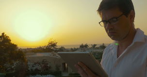 Businessman using touch pad in the evening. Businessman using touch pad against sunset on tropical resort, then he takes off glasses to rub his eyes stock video