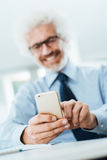 Businessman using a touch screen phone Royalty Free Stock Images