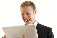 Businessman using touch screen tablet computer. Laughing young businessman using touch screen tablet computer Stock Photos