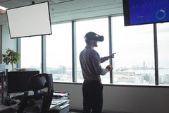 Businessman using virtual reality glasses against glass windows Royalty Free Stock Images