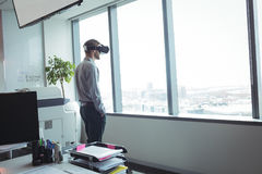 Businessman using virtual reality glasses at office. Businessman using virtual reality glasses by glass window at office Stock Photography