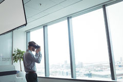 Businessman using virtual reality glasses while standing at office Stock Photography
