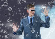 Businessman with using virtual reality headset holding connecting icons Stock Image