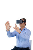 Businessman using vr glasses while sitting on chair Royalty Free Stock Images