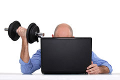 Businessman using weights Stock Images