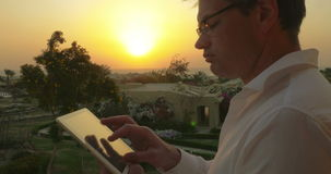 Businessman on vacation using touch pad at sunset. Young man outdoor at sunset. He putting on glasses and starting to work with tablet computer. Business on stock footage