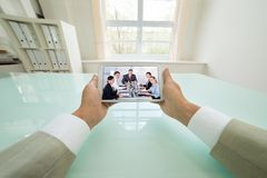 Businessman video chatting with colleagues Stock Images