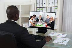 Businessman Video Chatting With Colleagues On Computer Stock Photos