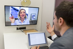 Businessman on video conference with her colleague in office job Royalty Free Stock Photos