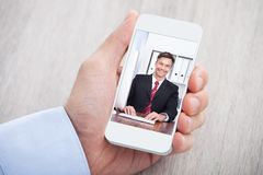 Businessman video conferencing with colleague at desk Stock Photo